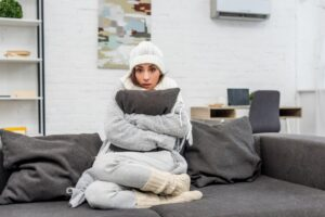 woman-wrapped-in-robe-hugging-pillow-looking-cold