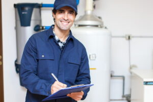 smiling-technician-ni-=front-of-tank-water-heater
