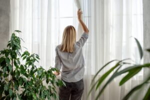 woman-adjusting-curtain-inside-home